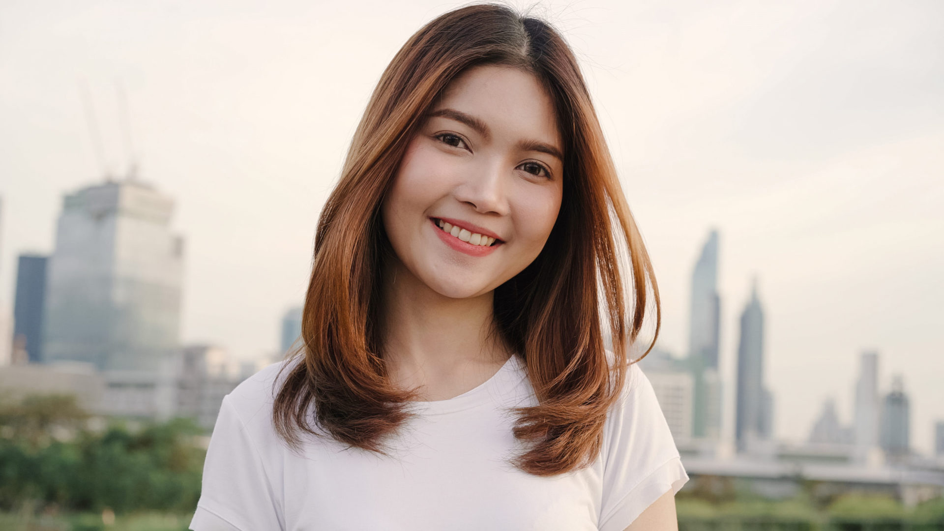 Cheerful beautiful young Asian woman feeling happy smiling to camera while traveling on the street at downtown city. Lifestyle backpack tourist travel holiday concept. Portrait looking at camera.